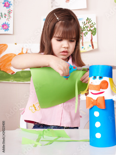 Serious child cutting paper.