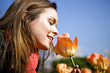 A young woman smelling a tulip, close-up