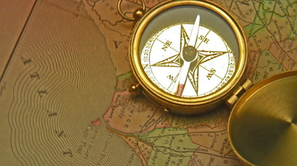 Old brass compass over antique map
