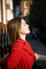 A young woman in a red coat enjoying the sun