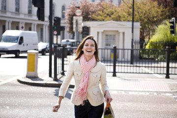 A young woman crossing the street, smiling