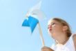 Leinwanddruck Bild - Closeup of little girl blowing blue wind wheel