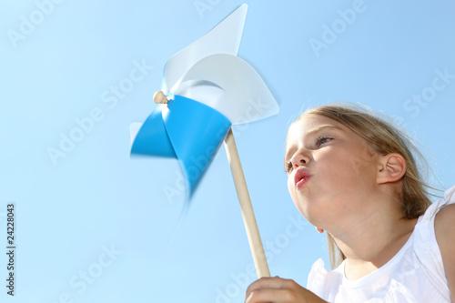 Leinwanddruck Bild Closeup of little girl blowing blue wind wheel