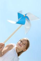 Closeup of little girl blowing blue wind wheel
