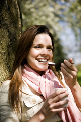 A young woman eating a yoghurt, outdoors