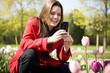 A young woman photographing flowers with her phone