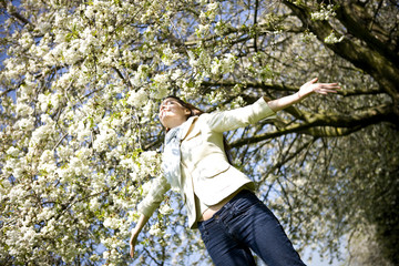 A young woman standing under a tree, arms outstretched