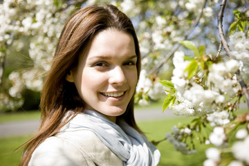 Portrait of a young woman standing next to a tree in blossom