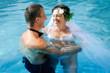 glückliches Brautpaar lacht im Wasser eines Schwimmbades