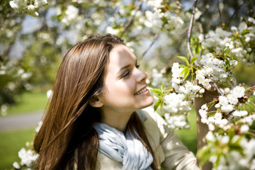 A young woman looking at spring blossom