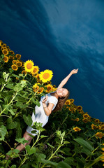 Girl inside sunflowers field over clody sky