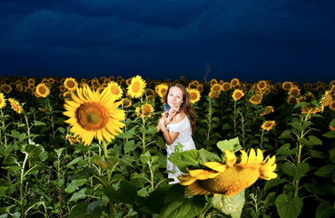 Girl inside sunflowers field over cloudy lightning sky