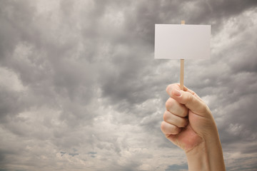 Man Holding Blank Sign Over Dramatic Storm Clouds