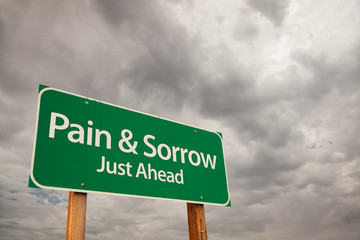 Pain and Sorrow Green Road Sign Over Storm Clouds