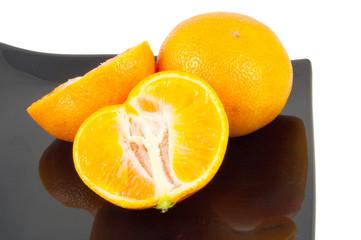 cut segmented orange on black plate on white