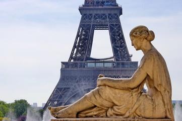 Femme assise au pied de la tour Eiffel