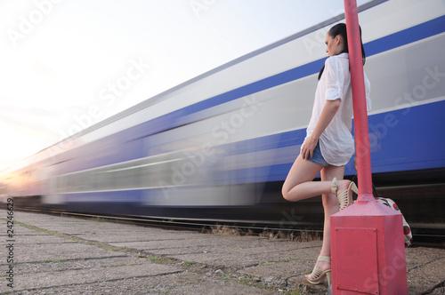 single lady on platform looking at vanishing train
