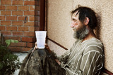 Sad homeless man sitting on at the wall on city street - Fine Art prints