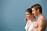 Couple in swimwear enjoy water and sun at sea poster