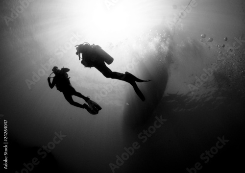 scuba divers silouetted by sun ball - 24264047