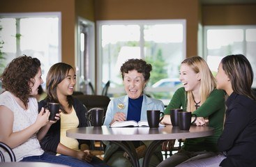 Group Of Girls Listening To Senior Woman In Restaurant