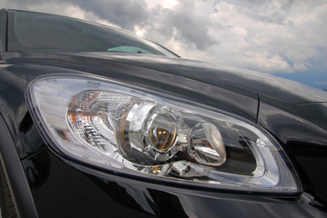 modern european car headlight against stormy sky