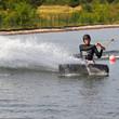 Mann Sportler beim Wakeboarden Wasser spritzen
