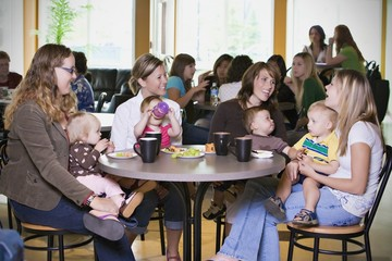 Group Of Young Mothers Relaxing In Cafe