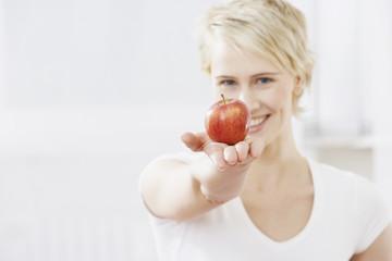 Junge Frau mit einem Apfel in der Hand