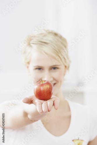 canvas print picture Junge Frau mit einem Apfel in der Hand