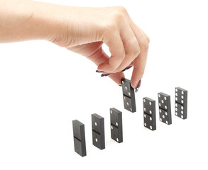 The hand builds a line of dominoes on a black background