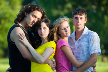 Four young people embrace and stand in the park