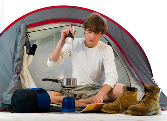 Man in a tent outdoor and cooking
