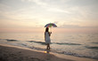 Young beautiful girl on the beach at sunrise with umbrella.