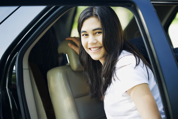Beautiful teen girl by car door