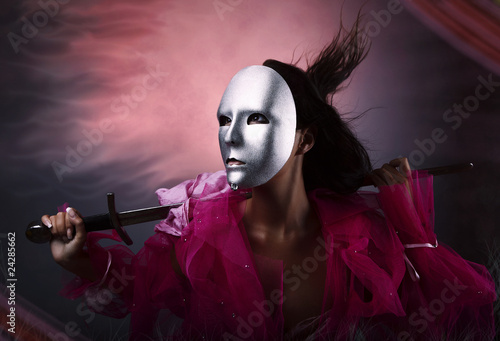 Woman warrior in a silver mask with a sword in hands.