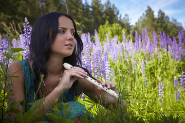 Attractive girl with a flute sitting in a summer field.