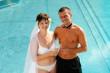 Brautpaar in Badekleidung mit Sektgläsern vor Pool