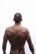 Trained male's back with tattoo