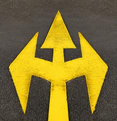 drei gelbe Pfeile auf Asphalt