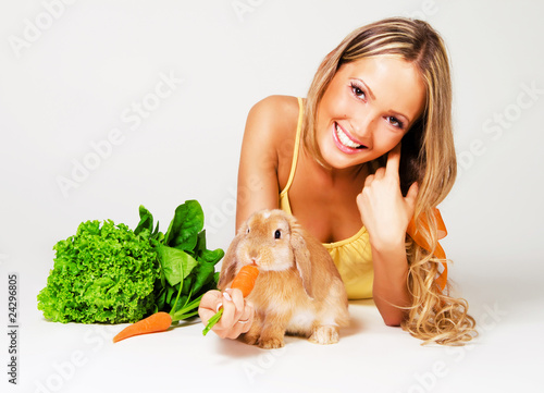 Pretty cheerful girl feeding a rabbit