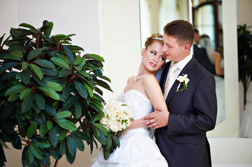 Happy bride and groom about green tree