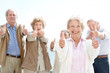 Lovely old woman showing thumbs up sign with her friends