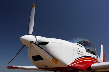 Motorflugzeug in Weiss-Rot-Blau vor blauem Himmel