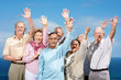 Group of mature friends standing with raised hands