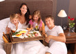 family having breakfast in bed