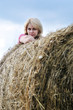 young woman and huge haystack