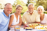 Adult Son And Daughter Enjoying Meal In Garden With Senior Paren