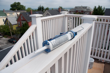 Caulking Gun on Rooftop Deck Railing