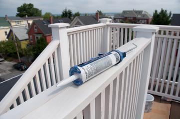 Caulking Gun on Rooftop Deck Railing